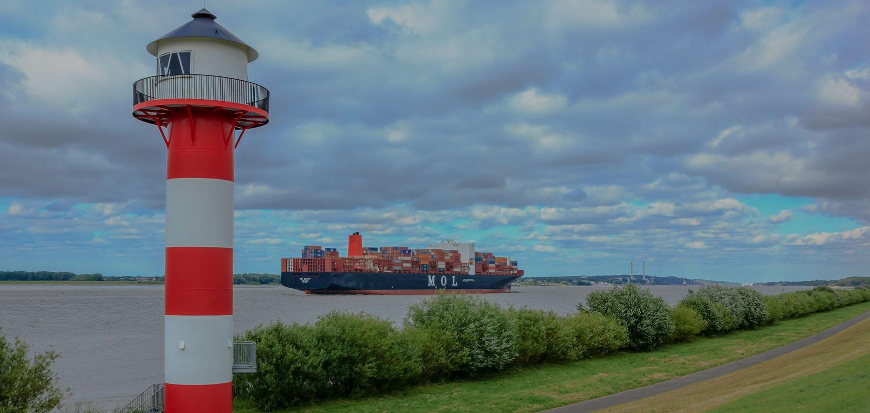 Leuchtturm und Containerschiff an der Elbe im Alten Land