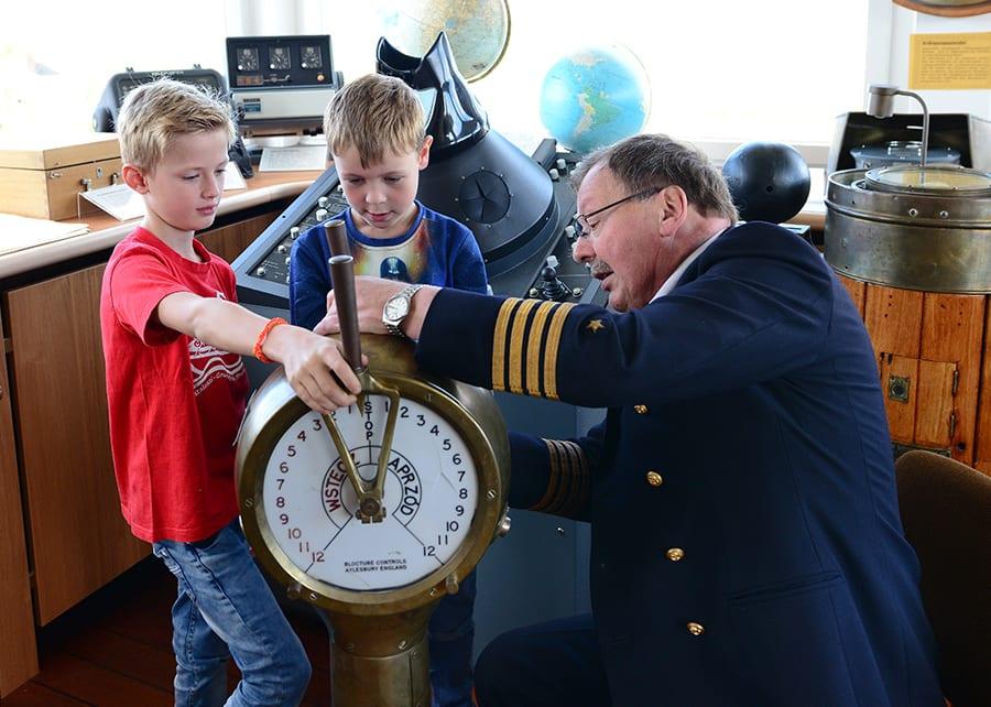 Kapitän mit Kindern auf der Kapitänsbrücke